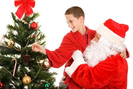 Santa lifts a little boy up to get a candy cane from the top of the Christmas tree.  White background. Stock Photo - 3876411