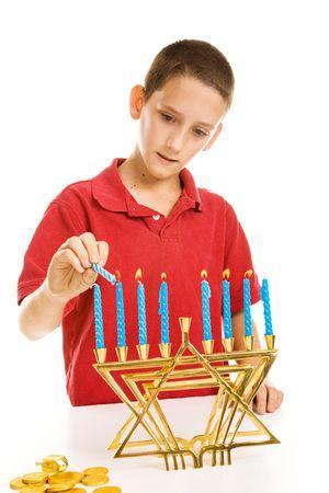 gelt: Young boy lighting the menorah for Hanukkah.  Isolated on white.