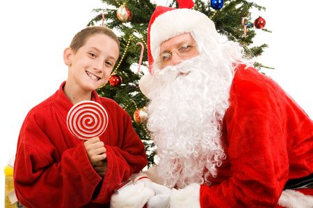 Adorable little boy holding a lollipop, together with Santa Claus.  White background.