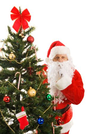 christmas costume: Santa Claus peeking around the Christmas tree gesturing for you to be quiet.   Stock Photo