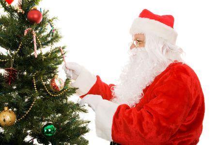 サンタ クロースがクリスマス ツリーを飾るします。 白い背景上に分離。 写真素材