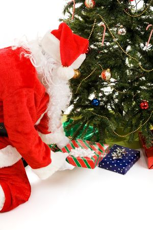Santa Claus putting presents under the Christmas tree.  Isolated on white. Stock Photo - 3876408