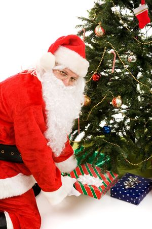 Santa putting Christmas presents under the tree.  Isolated on white. Stock Photo - 3876401