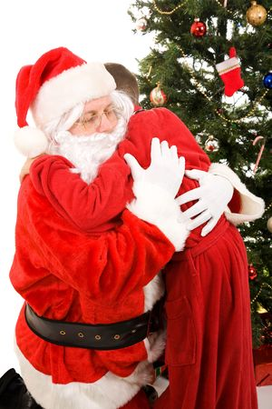 Santa Claus getting a big hug from a child on Christmas morning.  White background. Stock Photo - 3876406