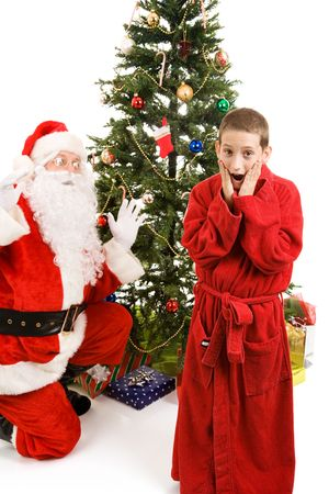 christmas morning: Little boy shocked to discover Santa Claus on Christmas morning.  Isolated on white. Stock Photo