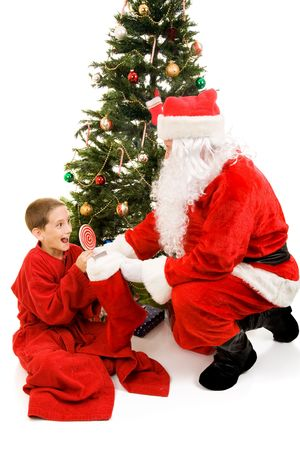 Very excited little boy getting his Christmas stocking from Santa Claus.  Isolated on white.   Stock Photo