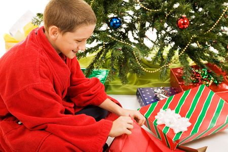 Cute little boy opening his presents on Christmas morning.   photo