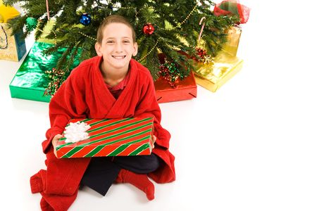 Adorable little boy holding a Christmas present.  Isolated on white background.