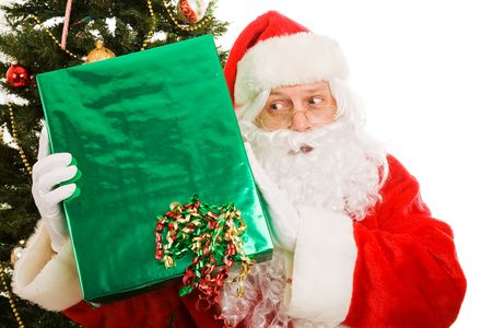 Santa Claus shaking a Christmas present to guess what is inside.  White background Stock Photo - 3889929