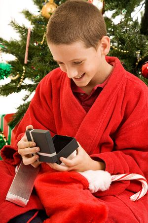 christmas morning: Adorable little boy opens gifts on Christmas morning.  Stock Photo