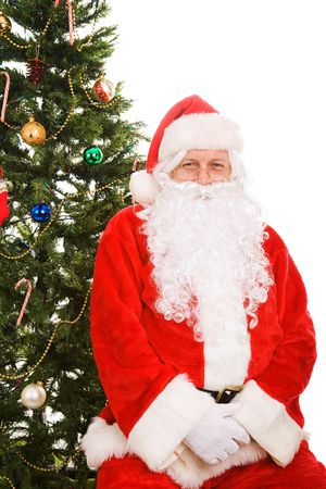 Santa Claus sitting under the Christmas tree.  Isolated on white. Stock Photo - 3889932