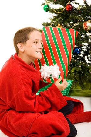 red bathrobe: Adorable little boy shaking a Christmas gift trying to guess whats inside.