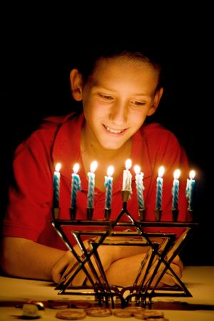 Little boy gazing on a lighted menorah, illuminated only by its light.  Shallow depth of field with focus on boy's eyes.