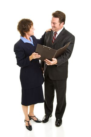 Attractive mature business man and woman going over a report.  Full body isolated on white. photo
