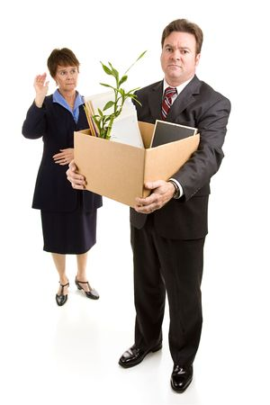 downsizing: Businessman loses his job due to corporate downsizing while a sad coworker waves goodbye.  Full body isolated on white.   Stock Photo