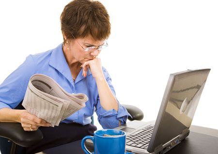 layoffs: Businesswoman checks the financial markets in the newspaper and online.  White background.