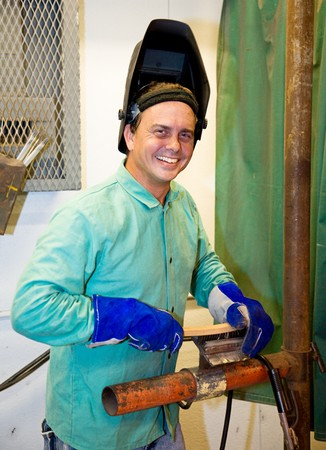 Friendly, smiling welder brushing metal filings off his latest project.