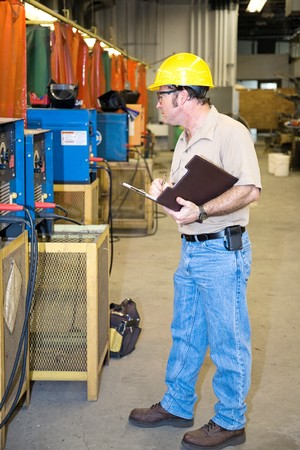 inspecting: Inspector performing a safety Check of welding equipment in a metal work factory.