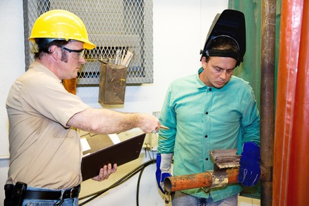 Supervisor evaluating a metal worker on the factory floor.   photo