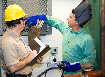 Welder in metal shop working while supervisor looks on. photo