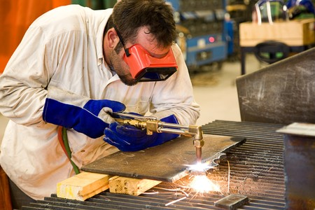 acetylene: Worker using an acetylene torch to cut through metal in a metalworks factory.   Stock Photo