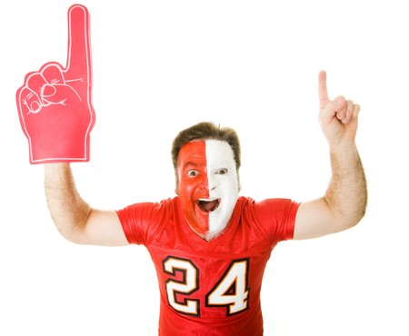 whit: Enthusiastic sports fan with foam finger raises his arms in the Number One gesture.  Isolated on whit.   Stock Photo