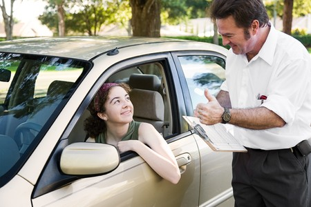 Teen girl passes her driving test and gets a thumbs up from her instructor.