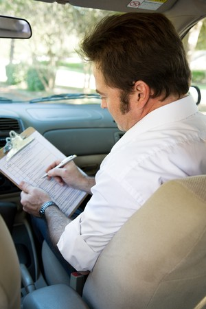 license: Instructor marks checklist during a driving test.  Focus on the instructor. Stock Photo