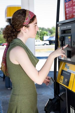 pagando: Joven mujer utiliza su tarjeta de cajero autom�tico para pagar la gasolina.