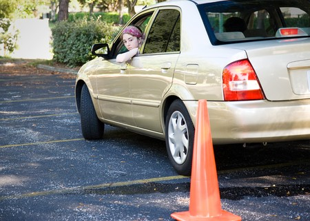 reverse: Teen driver backs up, doing the parking portion of her driving test.   Stock Photo