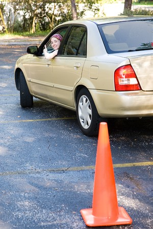 give out: Teen girl taking her driving test leans out the window to give an thumbs up.