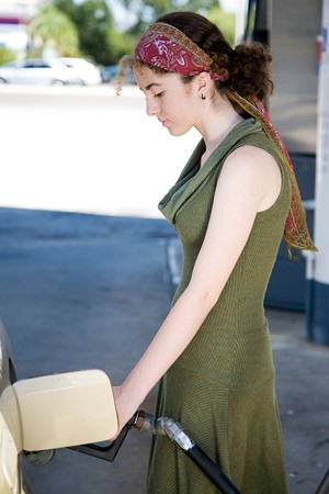 Teen girl pumping gas into the tank of her car.   photo