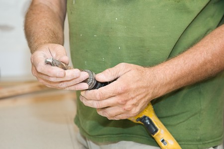 attaching: Contractor attaching 116 drill bit to his power drill.  Stock Photo