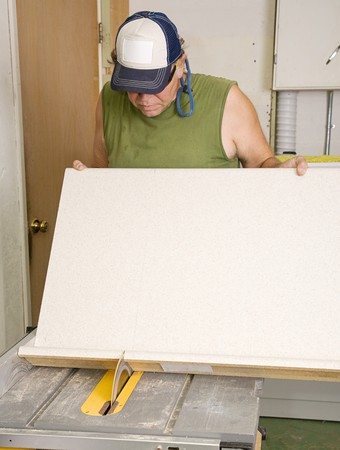 Carpenter using table saw to cut laminate counter top.  Focus on the saw. Stock Photo - 3993025