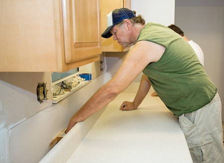 Contractor installing laminate counter top during a kitchen remodel.