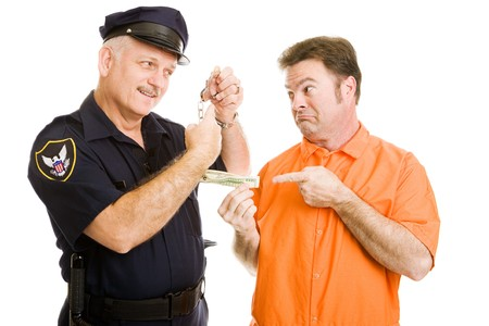 Prisoner offers policeman bribe.  Officer refuses and threatens handcuffs.  Isolated on white.   photo