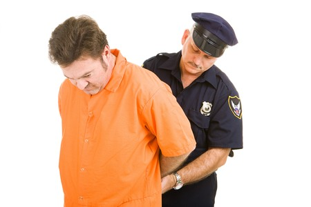Prisoner in orange jump suit being handcuffed by police officer.  Isolated on white. Stok Fotoğraf