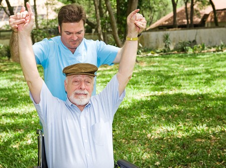 Senior man with arthritis is not enjoying his physical therapy session.   photo
