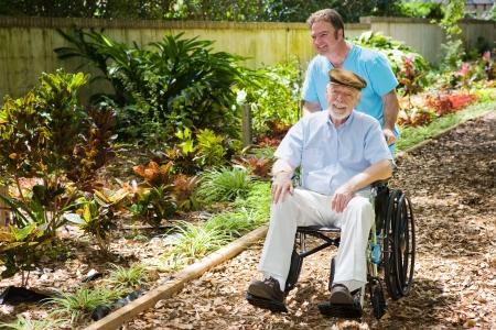 Con discapacidad superior al hombre que se empuja a través de un hermoso jardín con su enfermera.