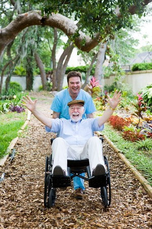 caring: Caring nursing home orderly pops a wheelie with an elderly mans wheelchair.  They are having fun.