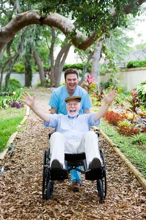 ordelijk: Caring verpleeghuis ordelijke verschijnt een wheelie met een oudere man rolstoel. Ze hebben lol.