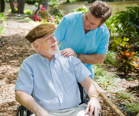 hospice: Disabled senior man in the garden with his male nurse.   Stock Photo