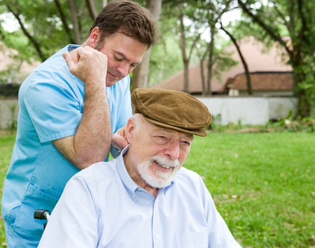 Massage therapist massaging a senior mans back in a beautiful outdoor setting.   photo
