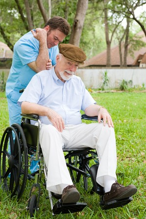 Disabled senior man receiving massage therapy in a lovely outdoor setting.   photo