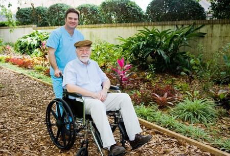 ordelijk: Verpleeghuis ordelijke neemt een senior man voor een wandeling in de tuin.