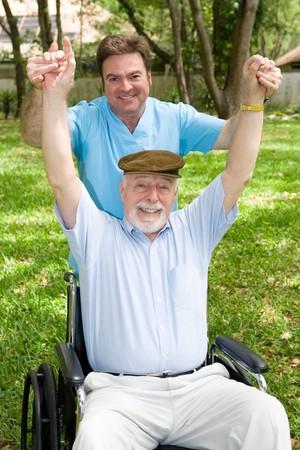 年配の男性人と気持が良い屋外のワークアウトを持っている彼の理学療法士。