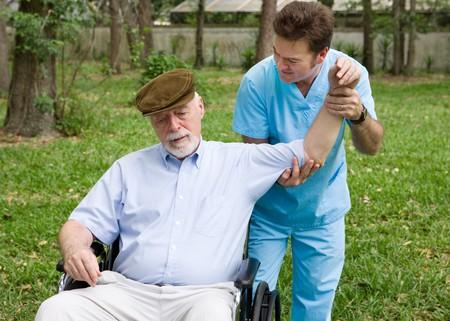 Fysieke therapeut werkt met een hoge man buiten in de frisse lucht.