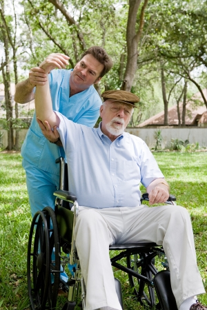 Physical therapist working with disabled senior man outdoors in a natural setting.   photo