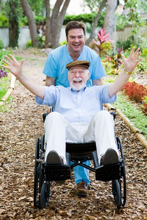 Caring nursing home orderly pops a wheelie with an elderly mans wheelchair.  They are having fun.
