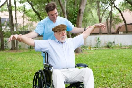 無効になっている年配の男性人は彼の物理的な療法士の助けを借りてストレッチ運動。
